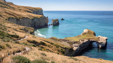 Tunnel Beach is a must-visit hidden marvel where a short track and tunnel opens up to a secluded beach.