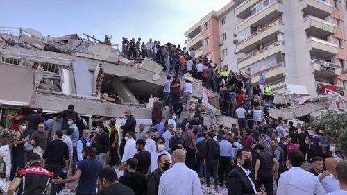 Kurtarma ekipleri ve yerel halk, Ege Denizi'nde Türkiye ve Yunanistan'ı sallayan şiddetli depremin ardından 30 Ekim 2020 Cuma günü İzmir'de yıkılan bir binanın enkazı altında mahsur kalan sakinlere ulaşmaya çalışıyor