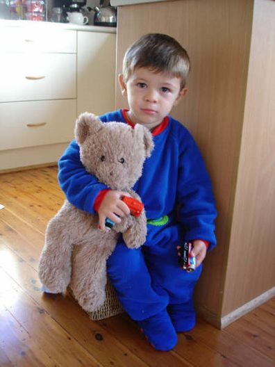 Isaac as a toddler holding a teddy bear