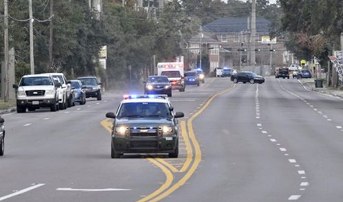 Police cars escort an ambulance after the shooting.