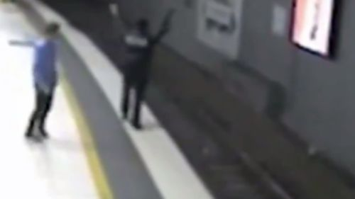 Mr Andrews could be seen waving his arms to flag down the train driver. (9NEWS)