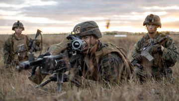 US Marine Private First Class Gabriel Gonzalez (centre), from 1st Battalion, 7th Marines, directs fire during an assault on Bowen Airport in Queensland, on Exercise Talisman Sabre 2021.