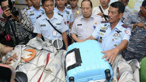 Indonesian Air Force commander Dwi Putranto shows debris including a suitcase found floating near where AirAsia flight 8501 disappeared. It was recovered by the Indonesian Navy. (AP)