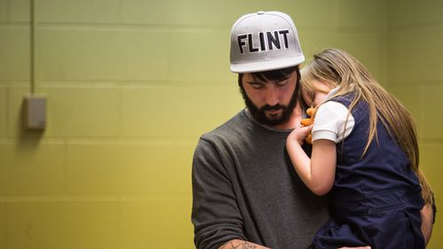 A Flint resident comforts a young girl after she gives blood to be tested for lead. (Getty)