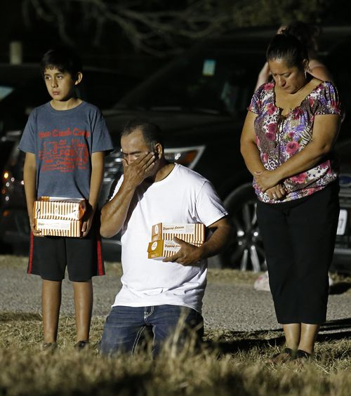 A man on his knees wipes tears from his face during a vigil a few blocks away from the shooting. (AAP)