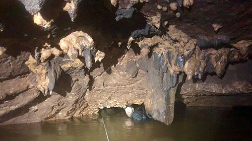 Senior Constable Justin Bateman tunnelling through the cave with the rope
