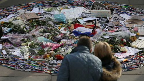 People look at a collection of pens and tributes during a memorial gathering for the victims of the recent terrorist attacks in France, in Trafalgar Square, London. (AAP)