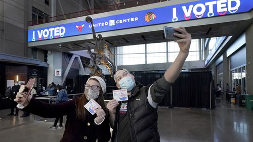 Samantha Jones and Peter Vina take selfies in the atrium of the United Center, transformed into a super voting site in Chicago.