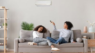 Woman and girl sit on couch above air conditioning.