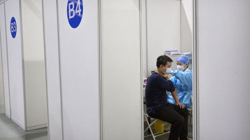 A medical worker gives a coronavirus vaccine shot to a patient at a vaccination facility in Beijing, Friday, Jan. 15, 2021