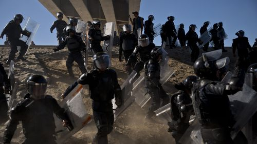 Mexican police run as they try to keep migrants from getting past the Chaparral border crossing in Tijuana, Mexico.