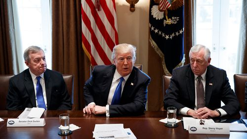 Senator Dick Durbin, D-Ill., left, and Representative Steny Hoyer, D-Md. listen as President Donald Trump speaks during a meeting with lawmakers on immigration policy in the Cabinet Room of the White House in Washington on January 9, 2018. (AAP)