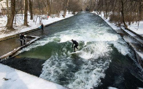 Brave surfers take to the wild water the Eisbach creek in the English Garden park in Munich, Germany. (AP).