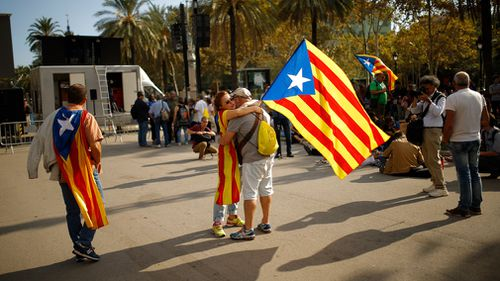 A woman holds a Catalan flag as she hugs a man during a rally in Barcelona, Spain. (AP)
