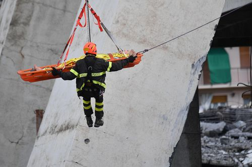 A survivor is winched to safety from the rubble below. Picture: AP