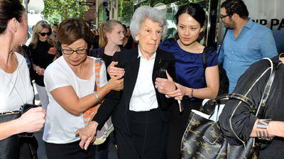 An elderly women is helped to walk near Martin Place. (AAP)