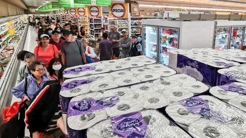 People awaiting their turn to purchase toilet paper, paper towel and pasta at Coles in Epping, Sydney.