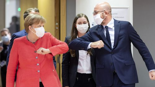 German Chancellor Angela Merkel (L) elbow bumps the President of the European Council Charles Michel (R) during an EU summit on July 17, 2020 in Brussels, Belgium. European Council President Charles Michel has called an extraordinary summit on Friday July 17 and Saturday July 18 to discuss the EU's post-coronavirus recovery plan and the 2021-2027 budget.