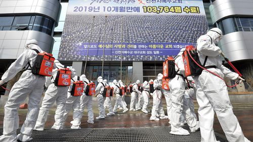 In this March 1, 2020, file photo, army soldiers wearing protective suits spray disinfectant to prevent the spread of the coronavirus in front of a branch of the Shincheonji Church of Jesus in Daegu, South Korea. As the coronavirus spreads around the world, many events that normally would draw large numbers of people are being canceled or played without fans. (Lee Moo-ryul/Newsis via AP, File)