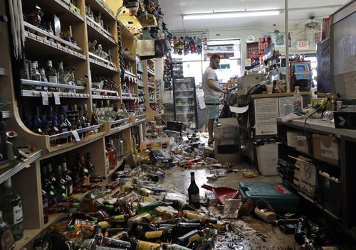 Bottles of alcohol and other products are strewn on the floor behind the main counter of the Eastridge Market on July 6, 2019, in Ridgecrest, California. Crews in Southern California assessed damage to cracked and burned buildings, broken roads, leaking water and gas lines and other infrastructure after the largest earthquake the region has seen in nearly 20 years jolted an area from Sacramento to Las Vegas to Mexico.