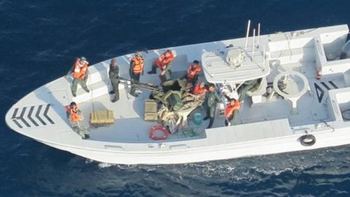 This image released by the US Department of Defence, taken from a US Navy helicopter, shows what the Navy says is the Islamic Revolutionary Guard Corps Navy after removing an unexploded limpet mine from the M/T Kokuka Courageous.