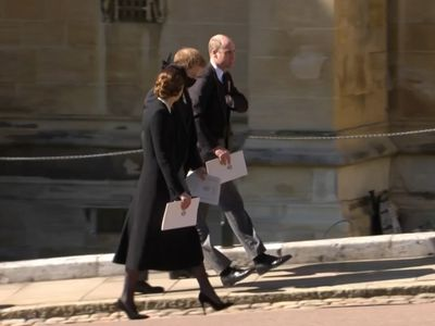 Kate, Harry and William walk together after the funeral