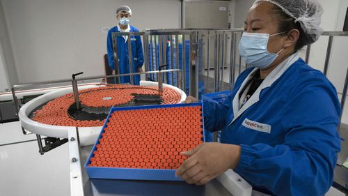 A worker feeds vials for production of SARS CoV-2 Vaccine for COVID-19 at the SinoVac vaccine factory in Beijing on Thursday, Sept. 24, 2020