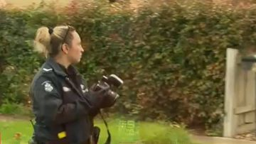 A police officer takes photos outside the scene of the alleged home invasion.