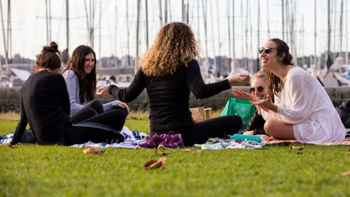 Friends catch up after lockdown restrictions ease at Rushcutters Bay Park in Sydney.