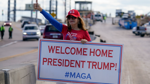 A supporter of President Donald Trump waits for the motorcade on the road to Mar-a-Lago, Trumps Palm Beach estate, on Wednesday, Jan. 20, 2021, in West Palm Beach, Fla. (AP Photo/Lynne Sladky)