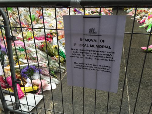 Flowers are being removed from the Sydney siege tribute at Martin Place ahead of forecast rain.
