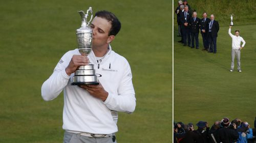 United States' Zach Johnson kisses the trophy as he poses for photographers after winning a playoff after the final round at the British Open Golf Championship at the Old Course, St. Andrews, Scotland. (AAP)