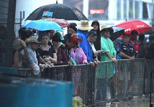 Fans at the GC600 Supercars event on Surfers Paradise are lashed by rain before the event is cancelled.
