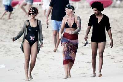 Rihanna visited family and friends in Barbados. And her bodyguard (the blonde) even flashed the paparazzi!