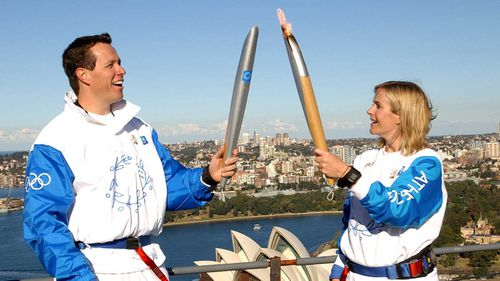 Zali Steggall during the 2000 Olympics torch relay, passing the flame over to Kieran Perkins on the Sydney Harbour Bridge.
