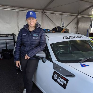 Emily Duggan race car driver next to her car