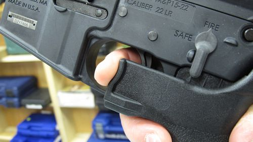 """An employee of North Raleigh Guns demonstrates how a """"bump stock"""" works at the Raleigh, NC shop. (AP)"""