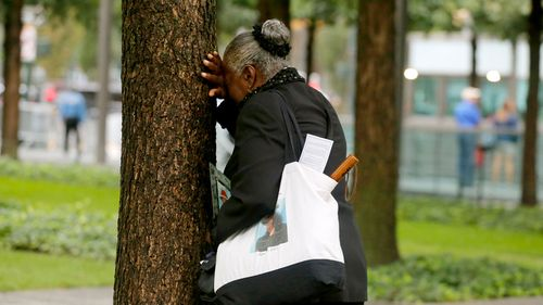 A woman weeps by herself as she leans against a tree during a ceremony marking the 17th anniversary of the terrorist attacks on the United States
