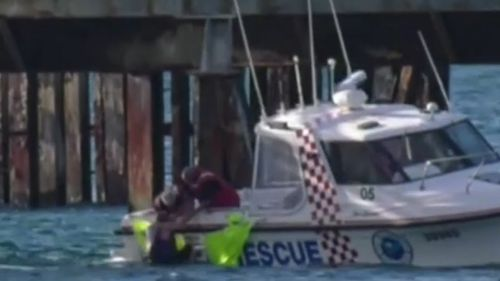 The man was found clinging to a jetty.