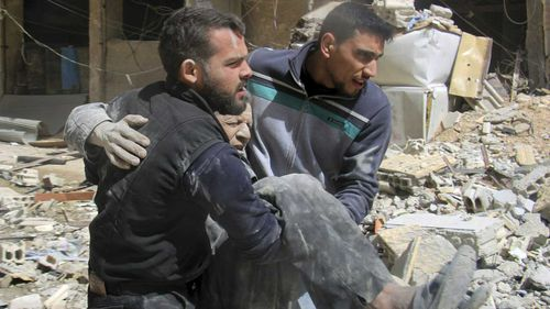 The White Helmets carrying a man who was wounded after airstrikes and shelling hit in Arbeen, in the eastern Ghouta region near Damascus. (AAP)