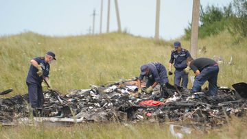 Search and rescue specialists inspect the crash area of MH17. (Getty)