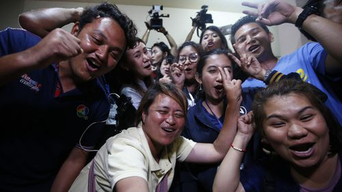 Thai media celebrate after learning the last of the group have been freed. Picture: AP