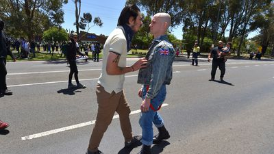 An anti-racism protester pushes a self-confessed skinhead at today's rally in Melton. (AAP)