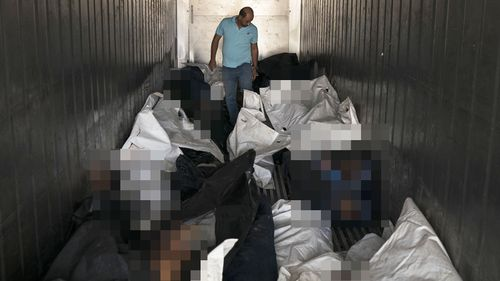 Medical assistant Sameh al-Azzawi walks inside a refrigerated container carrying dozens of bodies in a morgue in Mosul, Iraq. (AAP)
