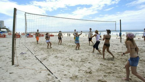 Recovery beach volleyball is popular on Surfers Paradise beach. (Image: AAP)