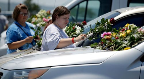Locals left flowers on a car believed to be owned by one of the victims. Image: AAP