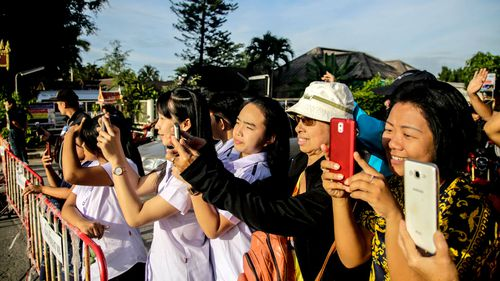 Onlookers watch and cheer as a helicopter flies towards an airstrip near where Thai authorities are in the process of rescuing the boys trapped in a cave with their soccer coach. (Getty)