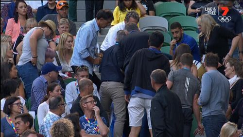 The crowd gathers around coach Nigel Sears after he collapsed.