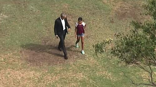Barack Obama takes a walk with a young girl in Government House gardens. (9NEWS)