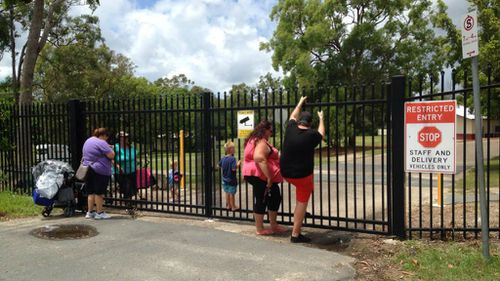 Parents anxiously await news outside of the school in Mabel Park. (9NEWS)